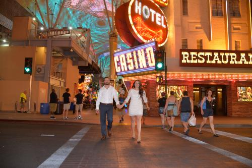 Photographers of Las Vegas - Wedding Photography - wedding couple at Fremont walking past the Vegas neon lights