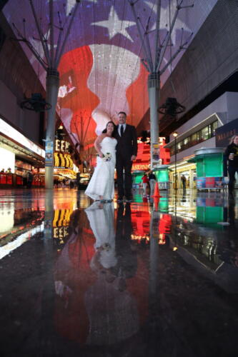 Photographers of Las Vegas - Wedding Photography - Couple reflected in rain water on Fremont Street